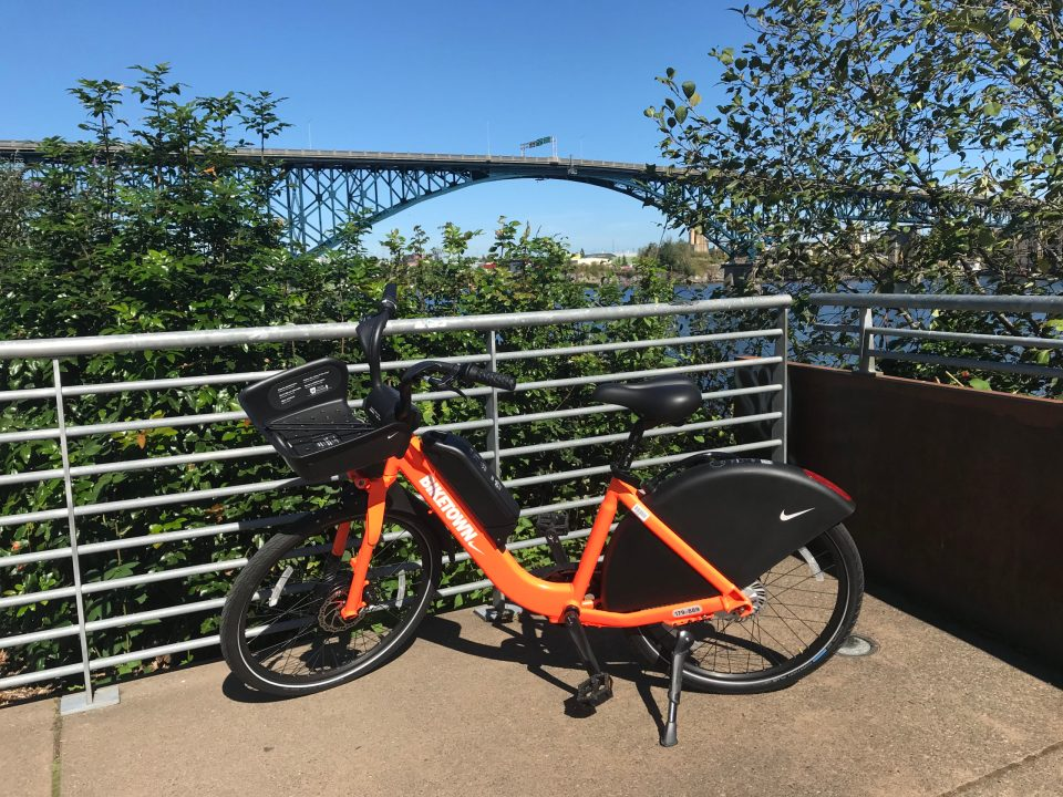 Photo of a BIKETOWN bike at a South Waterfront park with the Ross Island Bridge in the background.