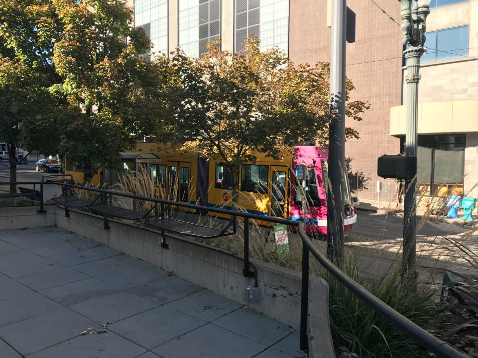 Photo of a pink and yellow streetcar behind trees at NW 13th and Lovejoy.