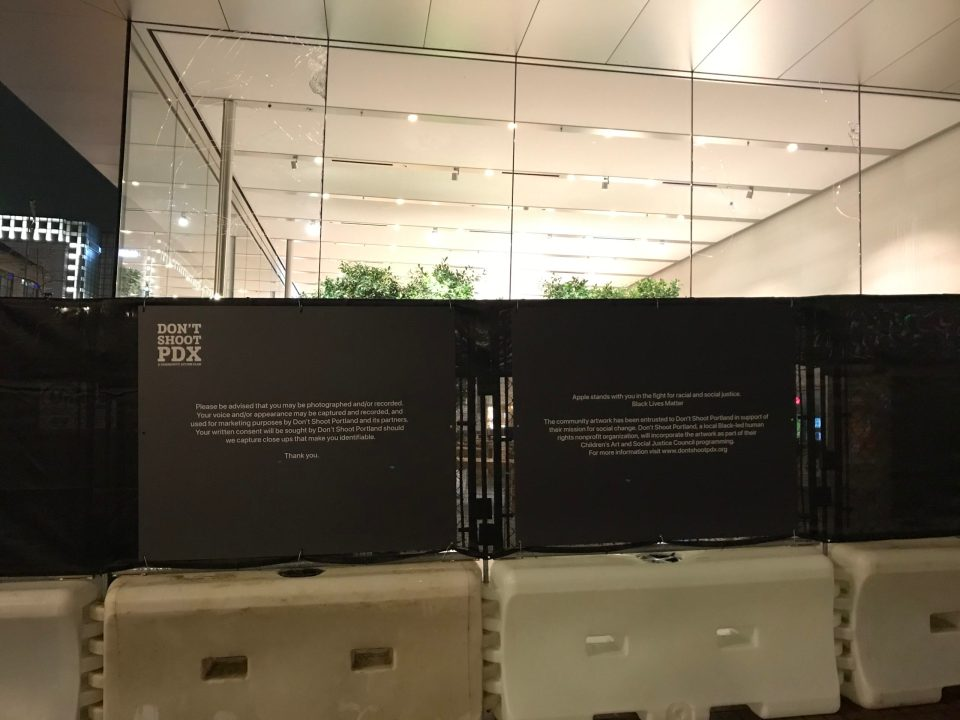 Photo of fencing around Apple Pioneer Place following the removal of a Black Lives Matter mural in preparation for repairs to the store.