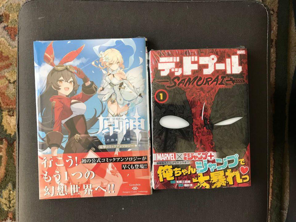 "Photo of a ""Genshin Impact"" manga and volume one of ""Deadpool Samurai""."