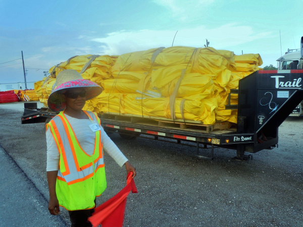 Etanisla Hernandez is a flag girl on the Hopedale cleanup site; she guides trucks and forklifts unloading protective barriers - Photo: Annie Correal