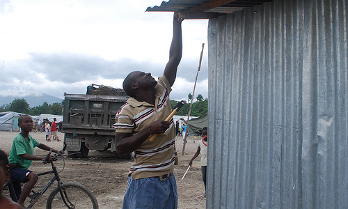 A man repairing his roof in Haiti - Photo: Oxfam International