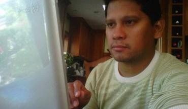 Reporter Elton Lugay peers at his laptop