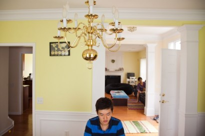 Alex Yoo sits in his Paramus, N.J. home while his guardian looks on from the living room. (Photo by Peter Moskowitz)