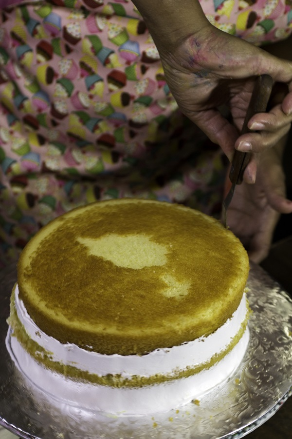 Andujar assembles the cake, putting a cake layer on a cardboard base, spreading on pineapple filling, then adding another layer and suspiro. The suspiro also helps to keep the cake moist, another signature of a good Dominican cake.