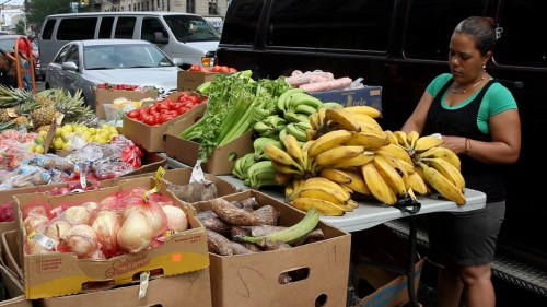 A vendor sells fruits and vegetables in Washington Heights. Photo by Maria Villasenor