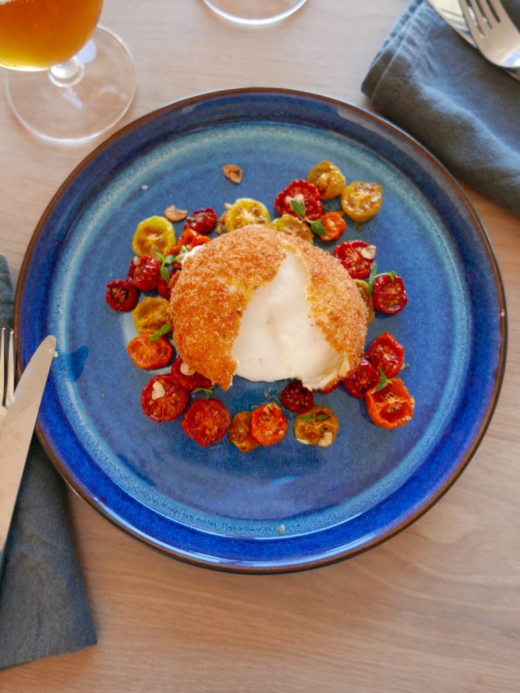 Friterad burrata öppen på tallrik med långbakade tomater