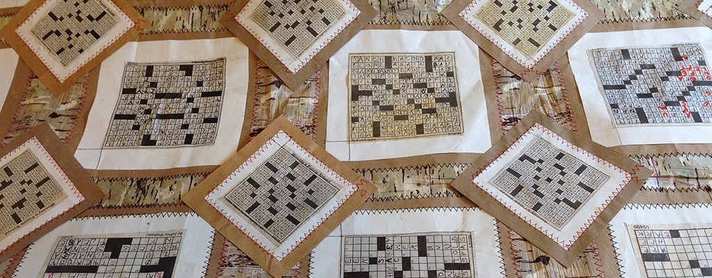 Quilt made of crossword puzzles in black, white, brown, and beige