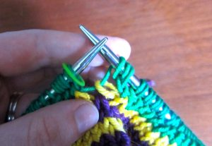 Slip the second loop of the last stitch to the right needle (do not knit it) and remove the marker.
