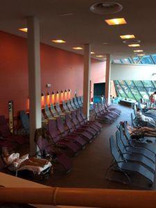 """Das Bild zeigt einen Innenbereich der """"Relax World"""" der Alpentherme. Die Aufnahme zeigt eine Reihe von Liegestühlen in Riehen von der Seite, dahinter eine rote Wand."""