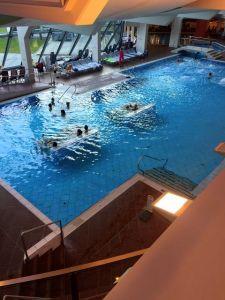 """Das Bild zeigt das große Becken der """"Relax World"""" der Alpentherme von oben. Auf Becken im Wasser liegen einige Personen. Im hinteren Bereich sind Liegestühle an einer großen, verglasten Fensterfront aufgereiht."""