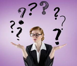 Hilfe bei Fibromyalgie: Fragen über Fragen. Das Foto zeigt den Oberkörper einer jungen Frau im Business-Kostüm vor lila Hintergrund. Sie hält beide Hände nach oben und darüber schweben Fragezeichen.
