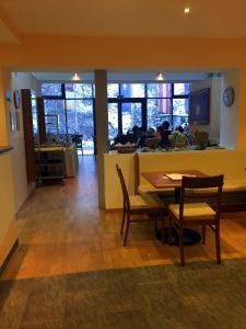 Das Bild zeigt das Bistro. Im vorderen Bereich steht ein Tisch mit zwei Stühlen. Der hintere Teil ist durch eine Bank getrennt und einen Durchgang links getrennt. Im hinteren Teil ist eine Glasfront zu sehen und einige Menschen, die an weiteren Tischen sitzen.
