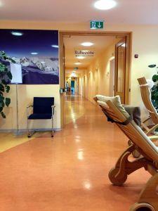Das Bild zeigt einen Gang im Kurhaus des Gasteiner Heistollens. Die Wände und der Boden sind in Gelb- und Orangetönen gehalten. Im Vordergrund sieht man zwei Liegen und einen Stuhl zum Ausruhen.