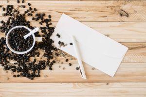 Auf einem Holztisch liegt ein weißer Briefumschlag, auf dem ein weißer Stift liegt. Daneben steht eine weiße Kaffeetasse, die voller Bohnen ist und in der ein weißer Löffel steckt. Viele Kaffeebohnen liegen um die Tasse verstreut.