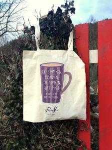 """Das Bild zeigt eine Stofftasche, die auf einer Parkbank liegt. Im Hintergrund ist ein Bach zu sehen.. Auf der Tasche ist eine lila Tasse aufgedruckt, auf der steht: """"Tief einatmen. Ausatmen. Tee trinken. Hilft immer. Im Notfall mit der Tasse werfen."""" Darunter ist das FibroFee-Logo und die Webadresse aufgedruckt."""