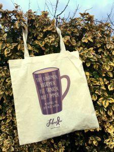 """Das Bild zeigt eine Stofftasche, die an einem Busch mit grün-gelben Blättern hängt. Auf der Tasche ist eine lila Tasse aufgedruckt, auf der steht: """"Tief einatmen. Ausatmen. Tee trinken. Hilft immer. Im Notfall mit der Tasse werfen."""" Darunter ist das FibroFee-Logo und die Webadresse aufgedruckt."""