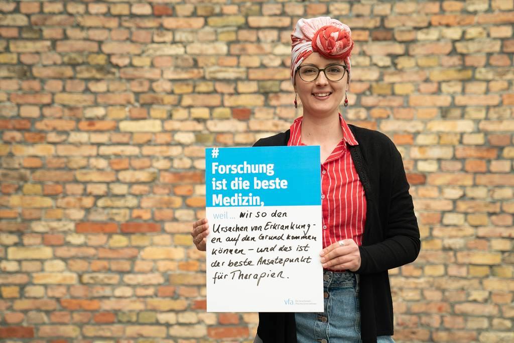 """Ein Text darüber, wie Schmerzmittel entstehen. Bild: Franzi steht vor einer Backsteinmauer und hält ein Schild. Auf dem steht der Satz: """"Forschung ist die beste Medizin, weil wir so den Ursachen von Erkrankungen auf den Grund kommen können - und das ist der beste Ansatzpunkt für Therapien."""""""