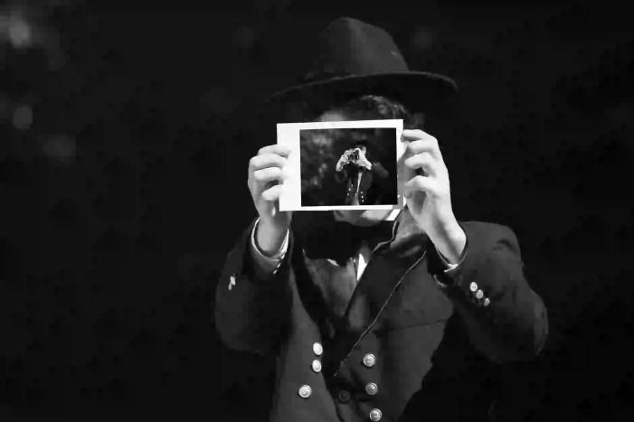 grayscale photo of person wearing hat and coat holding photo