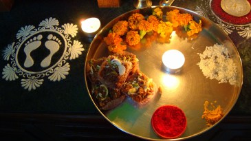 The 'Puja ki Thali' or a plate with the things required to successfully conduct a prayer. Some flowers, rice, turmeric, vermilion, and sweets.