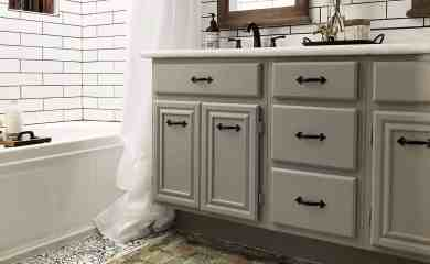 farmhouse style master bathroom with grey cabinets, stenciled floors, and turkish rug