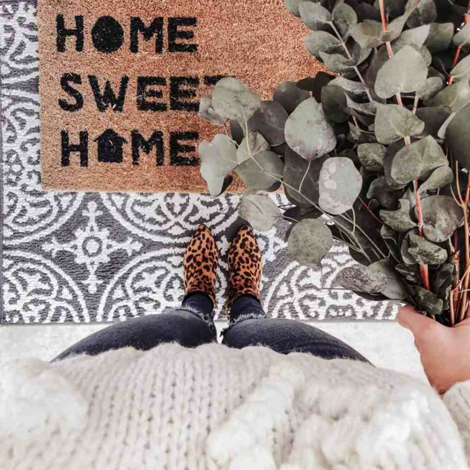 home sweet home door mat shot from above by girl holding eucalyptus bundle and wearing leopard print booties