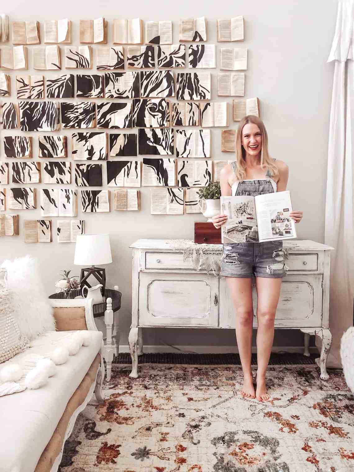girl standing in front of vintage book wall art installation and chippy white sideboard holding up a spread of the space as featured in San Diego magazine