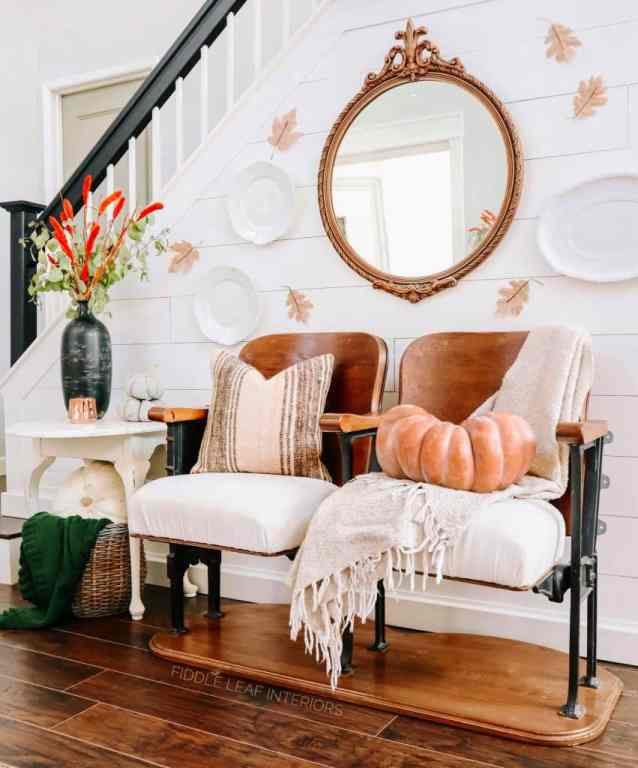 vintage theatre chairs sitting in front of white shiplap wall with burlap leaves stuck to wall and pale orange  sitting on chair - Fall Home Tour 2020