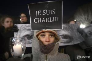 "Amandine Marbach from Strasbourg, France, takes part in a vigil to pay tribute to the victims of a shooting, by gunmen at the offices of weekly satirical magazine Charlie Hebdo in Paris, in the Manhattan borough of New York January 7, 2015. Hooded gunmen stormed the Paris offices of the weekly satirical magazine known for lampooning Islam and other religions, shooting dead at least 12 people, including two police officers, in the worst militant attack on French soil in decades. Sign reads ""I am Charlie"".    REUTERS/Carlo Allegri   (UNITED STATES - Tags: CIVIL UNREST CRIME LAW TPX IMAGES OF THE DAY) - RTR4KHDZ"