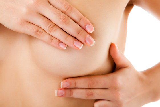 Woman examining her breast isolated on white