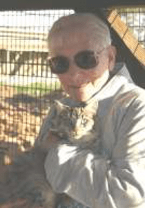 An elderly woman holding an elderly cat from the Mature Cats for Mature People program