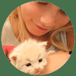 A FieldHaven volunteer holding a fluffy tan kitten.