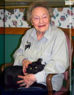 An elderly woman holding a black cat.