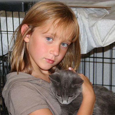 A little girl holding a kitten.