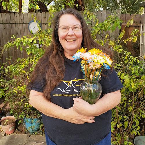 Volunteer Corinne Schrader holding flowers.
