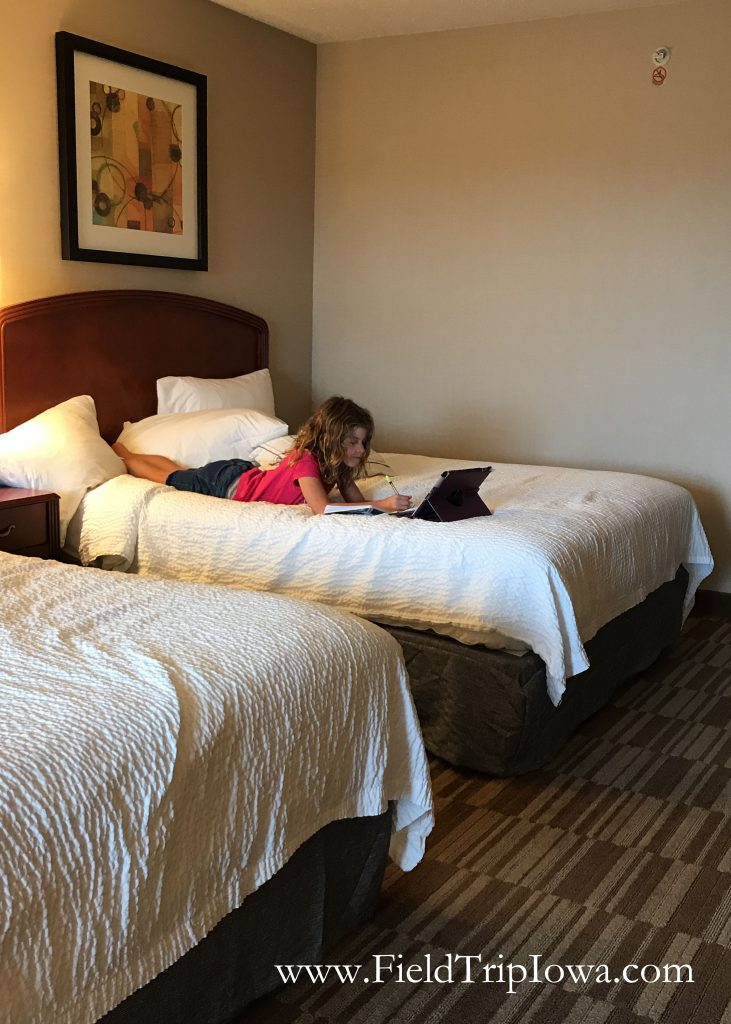 Girl on bed in a hotel room at Courtyard By Marriott in Roseville MN