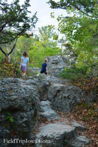 Children climb on rocks at trail at Backbone State Park on Backbone Trail in Iowa