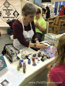 Women shows child how to use clay at Minnesota State Fair