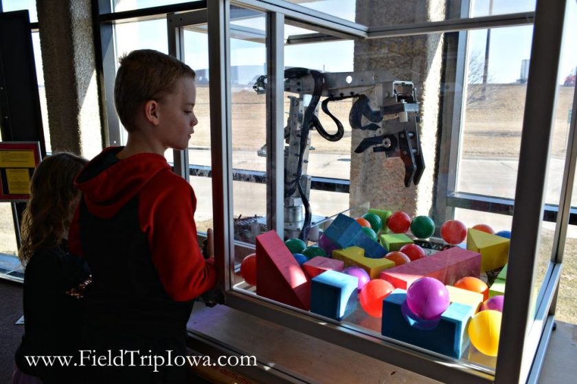 Boy plays with crane in Bluedorn Science Imaginarium in Waterloo Iowa.