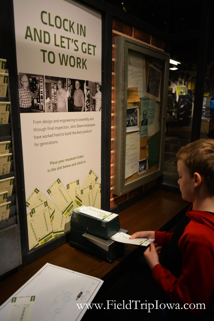 Boy uses punch clock at John Deere Tractor And Engine Museum in Waterloo Iowa.