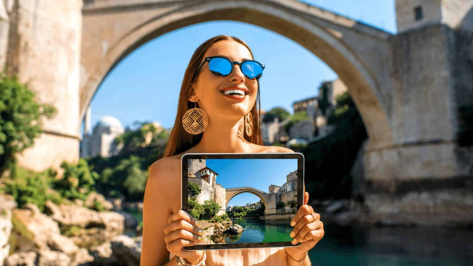 Tourist holding a tablet of the photo of a bridge that is behind her.