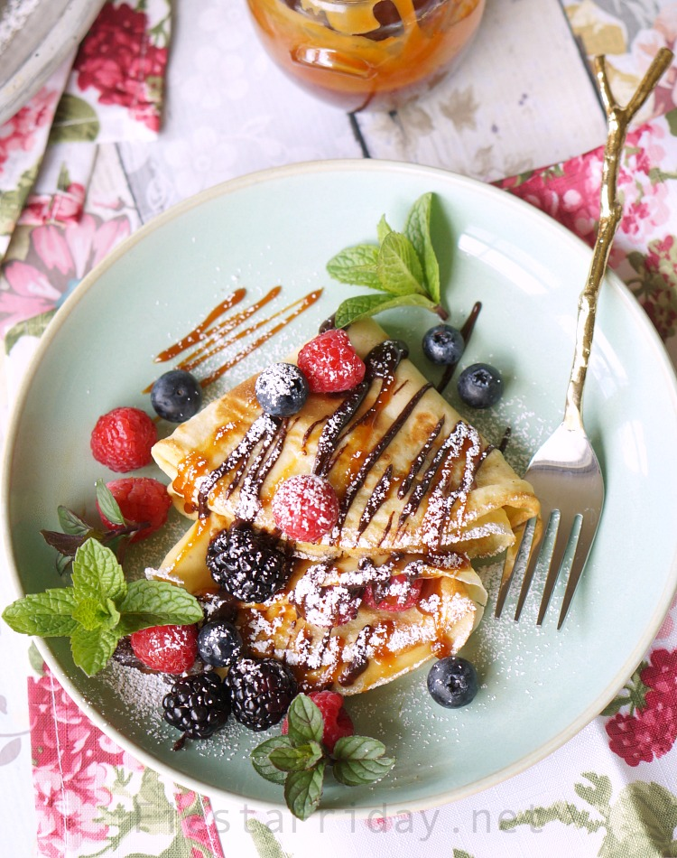 Chocolate Caramel Cream Cheese Crepes | FiestaFriday.net | Crepes are not at all hard to make, despite its French name, and they can be made sweet or savory. In this recipe, filled with cream cheese and served with berries and chocolate as well as caramel sauce, they make the perfect Mother's Day breakfast or dessert! #crepes #chocolate #caramel #creamcheese #dessert #snack #sweetsnack #easydessert