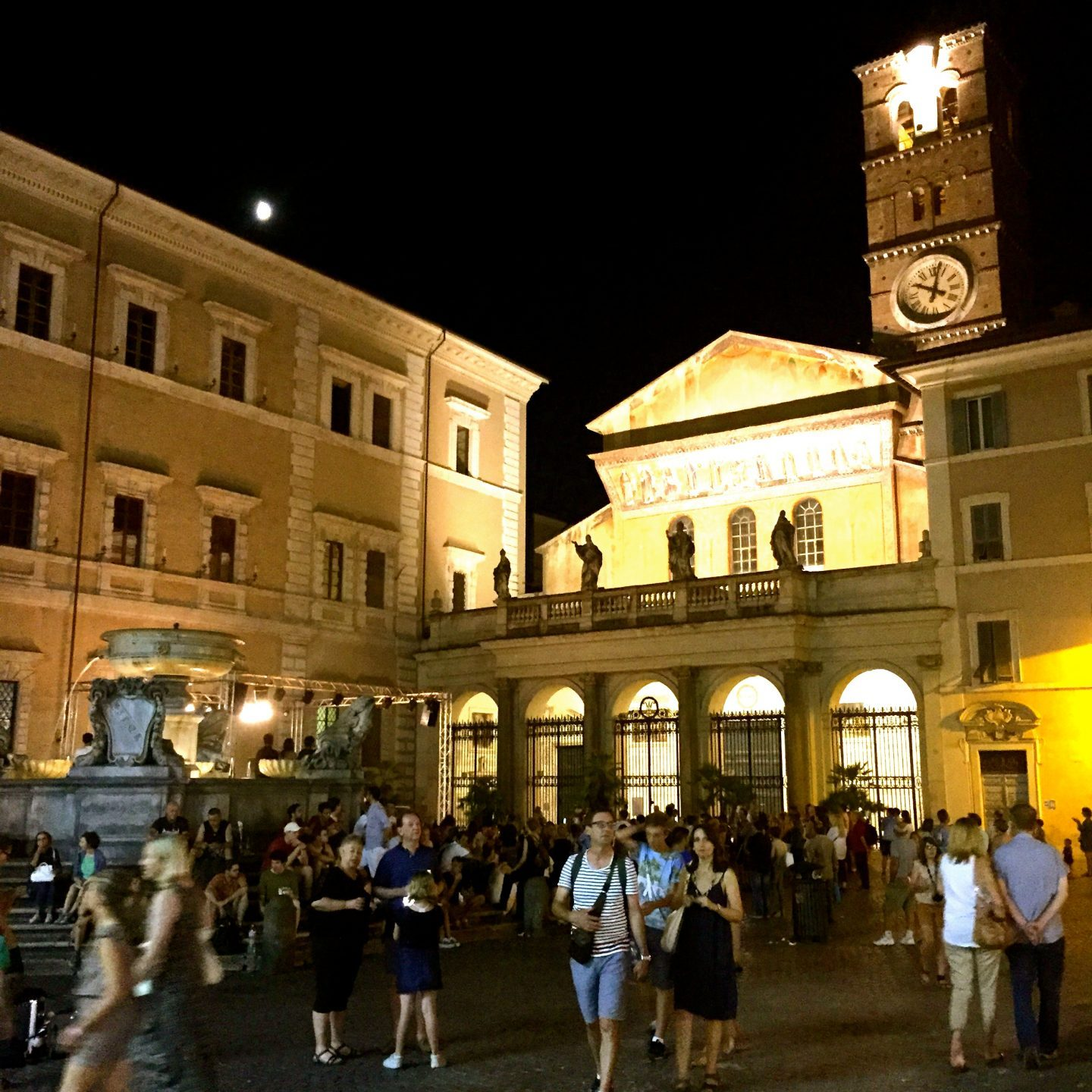 A bustling piazza in Rome lit up at night.