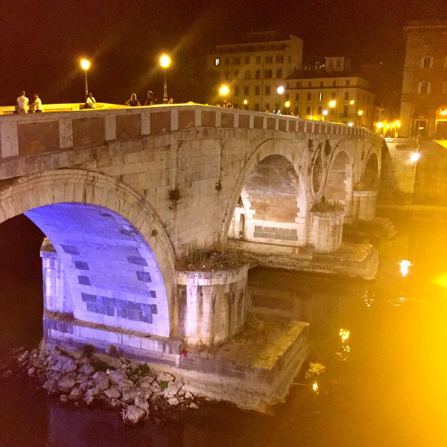 Crossing a bridge lit up at night in Rome to get to Trastevere.