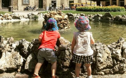 Kids looking at a fountain in Lucca on a summer family vacation with Katy from Untold Morsels.