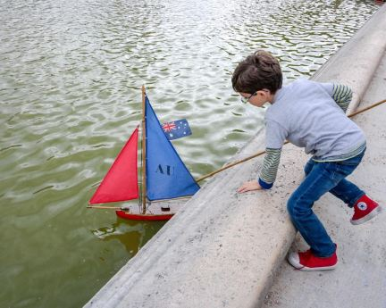 Playing with sailboats in the park water in Paris on a summer family vacation.