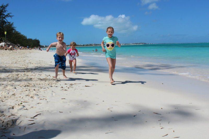 Kids running on the beach at Turks and Caicos.