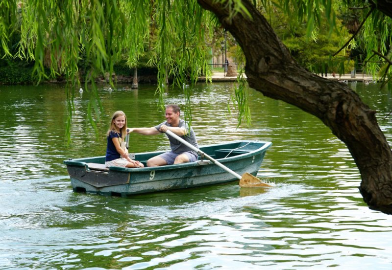 Father-daughter row boat ride at the lake in Ciutadella park in Barcelona.