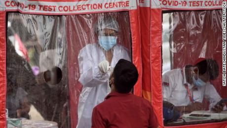 A healthcare worker collects swab samples at a Covid-19 testing center in Mumbai, India, on April 22.