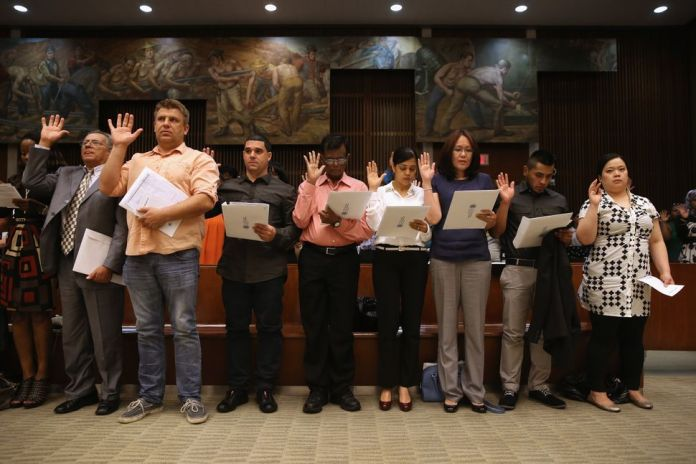Immigrants take the oath of allegiance during a citizenship ceremony in New York City in 2013 in front of Edward Laning's mur